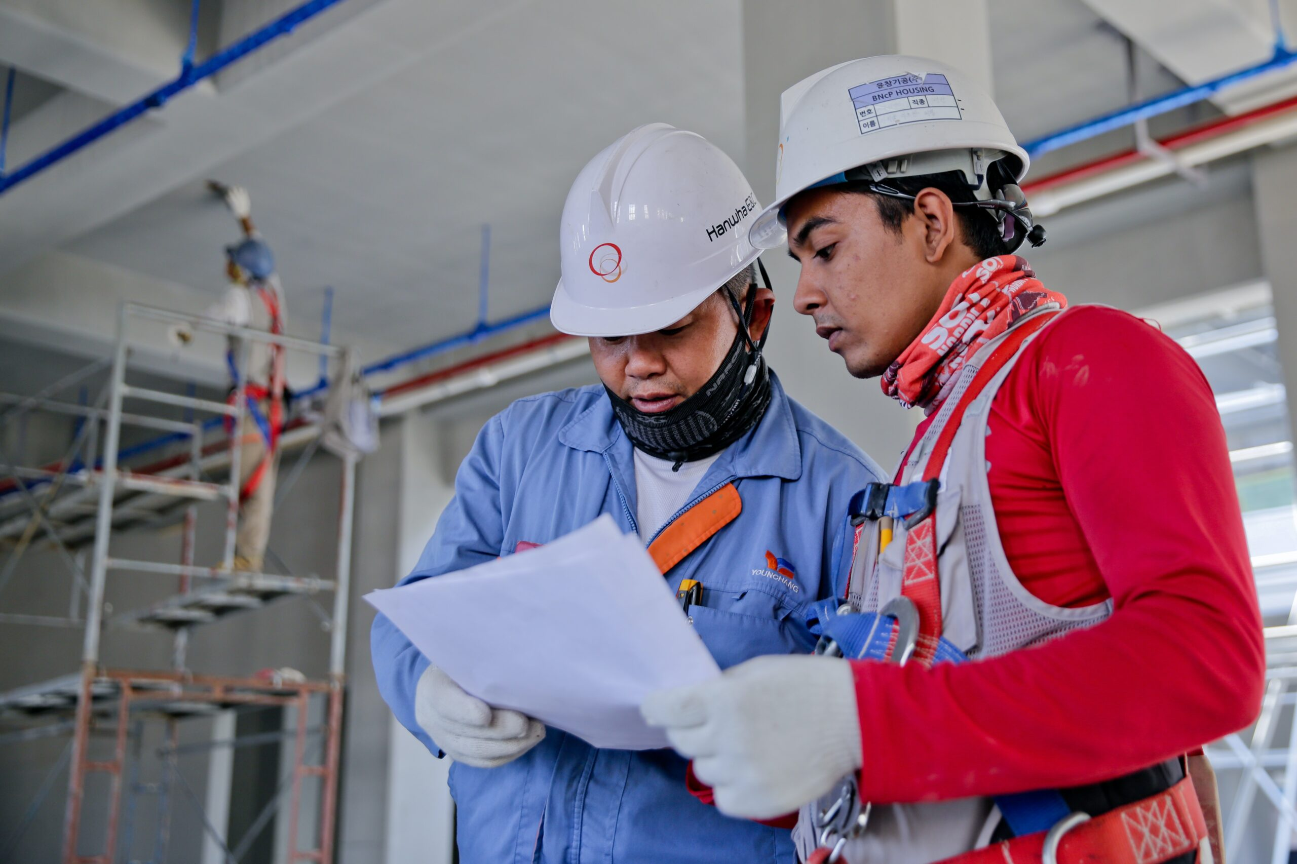 Construction workers looking at white paper